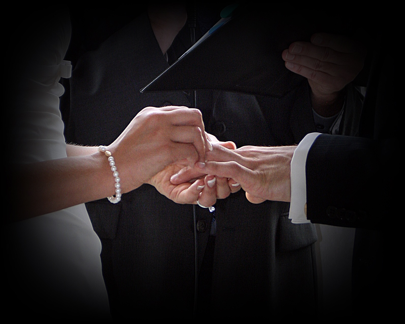 photo of bride putting ring on groom color photo