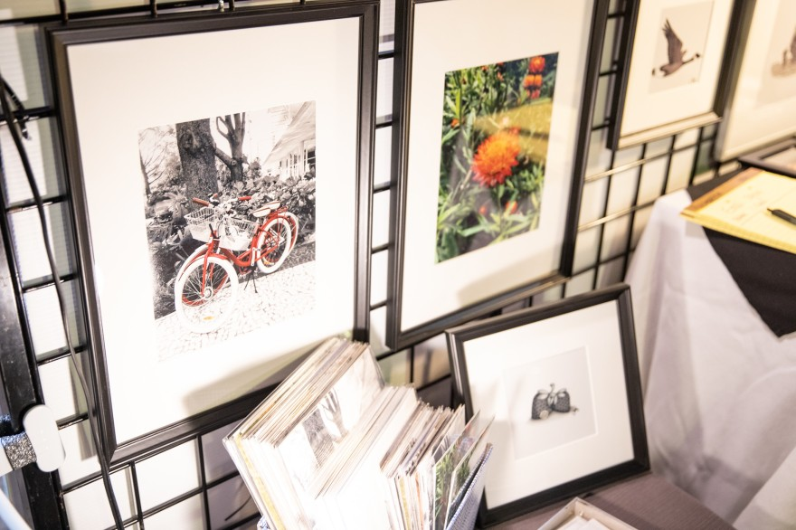 some of my framed photographs and box of prints. You can see a photograph of red bikes, a red and orange flower, and an illustration of a goose and strawberries.