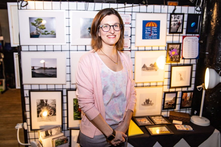 a photo of me standing in front of my display wall for the show, i am wearing a pink sweater an my glasses and behind me you can see a wall with my framed photographs and illustrations.