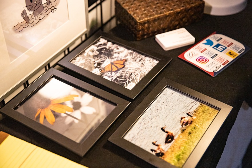 some of my framed photographs on a table you can also see business cards and qr codes to scan. the photos have ducks, or a monarch butterfly, or a black-eyed susan