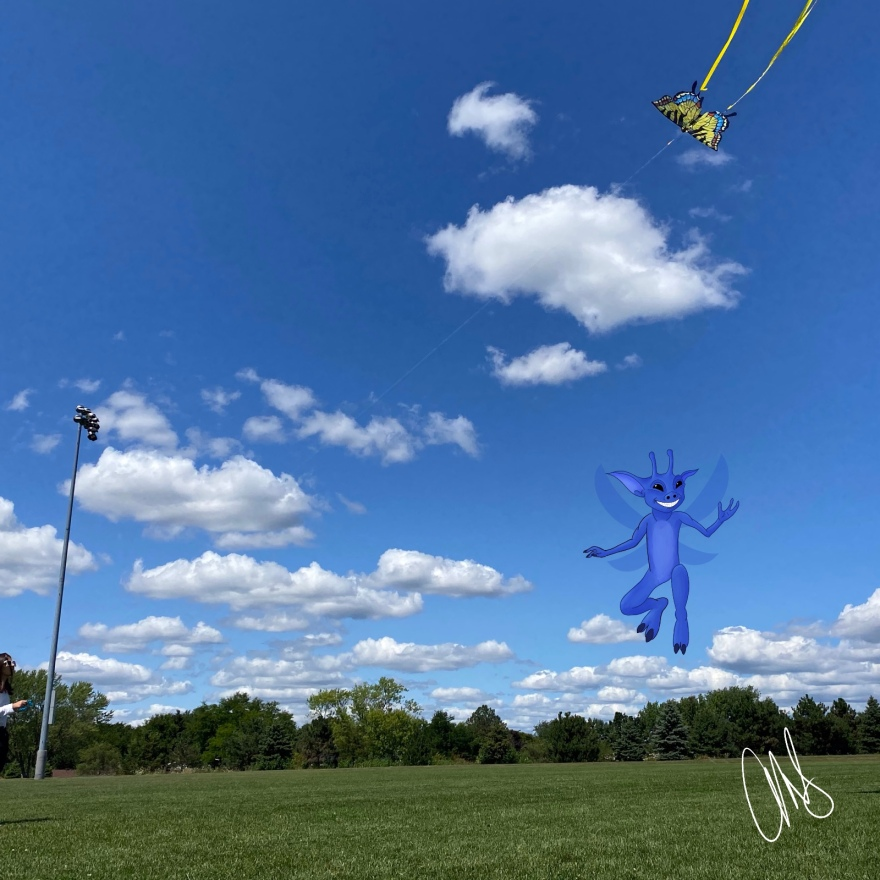 Photograph of a field with a blue sky and kite floating in upper right corner. clouds in the sky and illustration of pixie is flying off to middle right